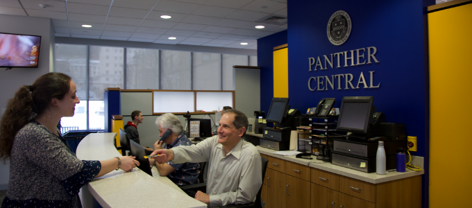 A photo of a Panther Central Customer Care Specialist assisting a customer.